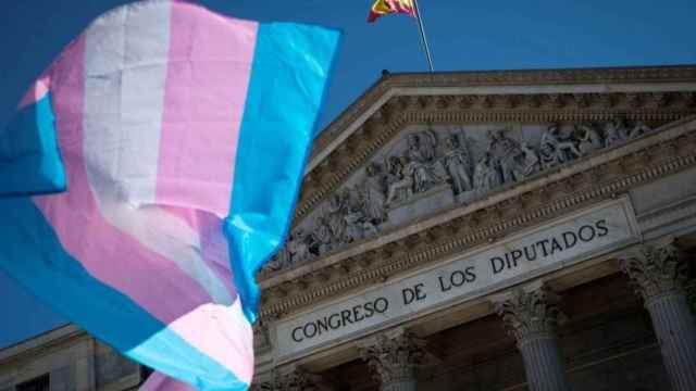Una bandera del colectivo trans ondea frente al Congreso de los Diputados.