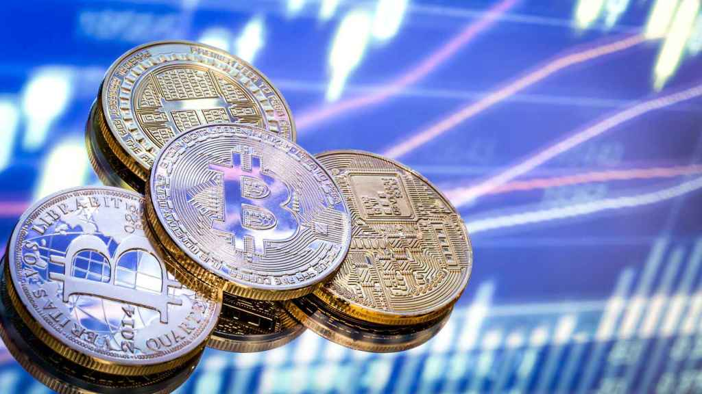 Varias monedas físicas de bitcoin en un montaje digital.