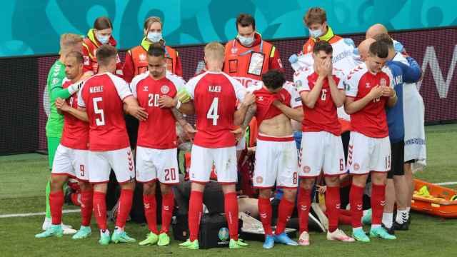 Los jugadores de Dinamarca rodean a Eriksen mientras es atendido