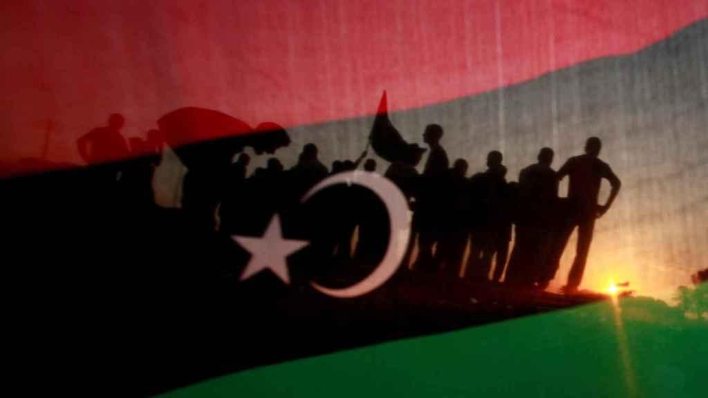Un grupo de libios apostados frente a la casa de Muamar el Gadafi y vistos a través de una bandera Libia.