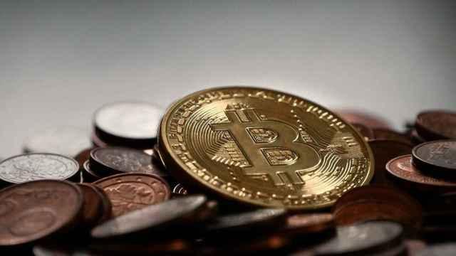 Una moneda de bitcoin entre otras de euro.