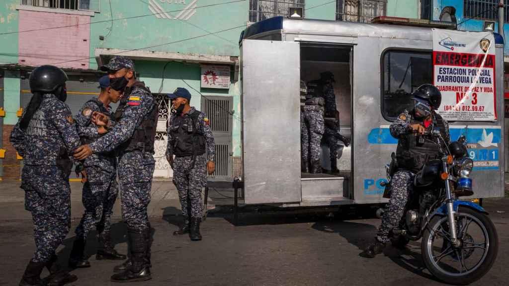 Miembros de la Policía Nacional Bolivariana montan guardia en la entrada de La Vega.