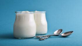 Dos yogures en recipientes de vidrio.
