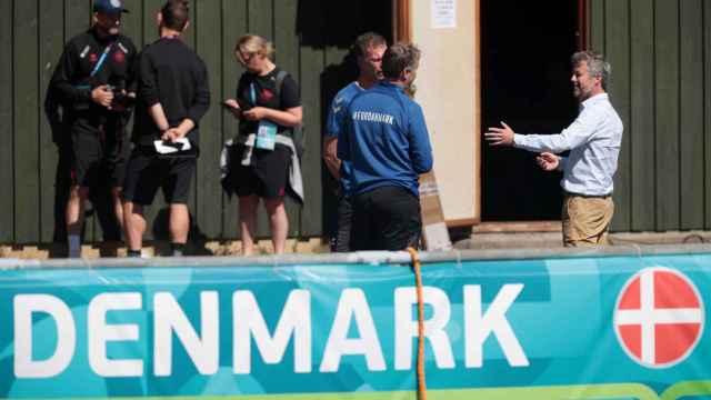 Kasper Hjulmand y varios miembros de Dinamarca conversan antes de un entrenamiento
