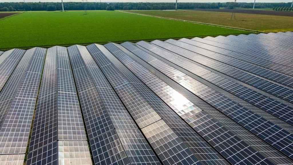 Paneles solares en primer plano con aerogeneradores al fondo.
