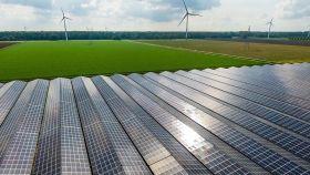 Placas solares con aerogeneradores al fondo.