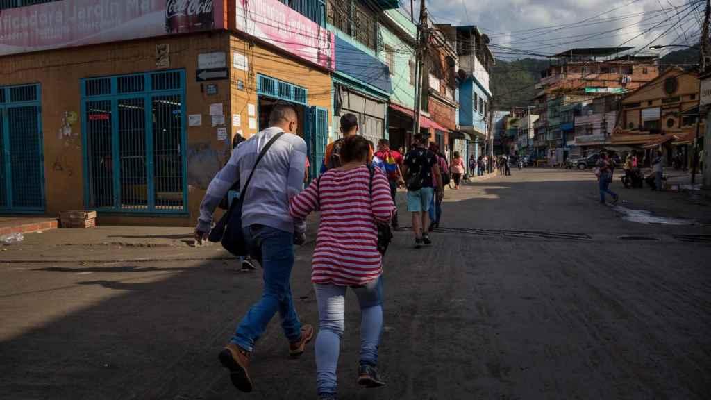 Un grupo de personas corre para cruzar una calle mientras suenan disparos en La Vega.