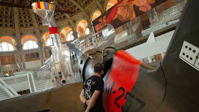 En primer plano, la reproducción del 'Mosca', con el bombardero 'Katiuska' suspendido del techo. Al fondo, detalle de la tabla 'La crucifixión de San Pedro'.