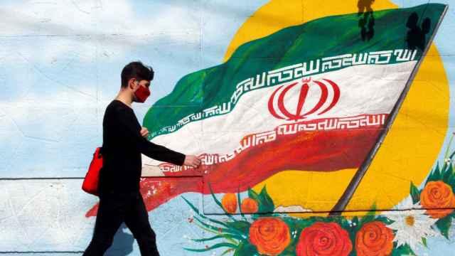 Un chico iraní pasa junto a un mural con la bandera nacional de Irán en una calle de Teherán.