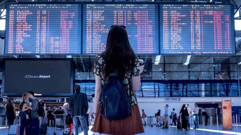 Una turista, frente al panel de destinos de un aeropuerto. FOTO: Pixabay.