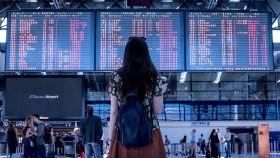 Una turista frente al panel de destinos de un aeropuerto.
