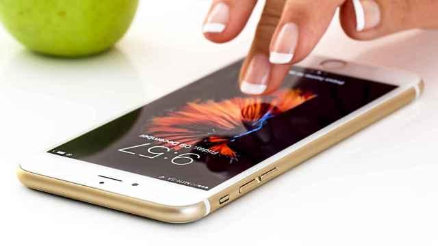 Una mujer maneja un teléfono móvil sobre una mesa.
