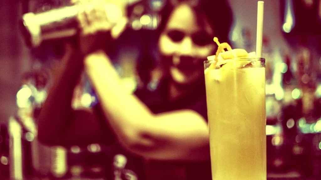 Una mujer barista prepara un combinado.