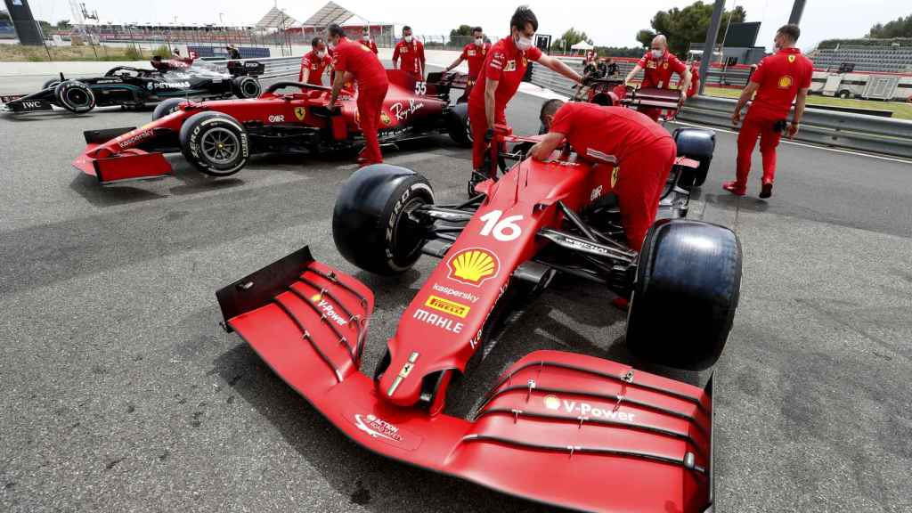 Mecánicos de Ferrari miran los monoplazas de Leclerc y Sainz