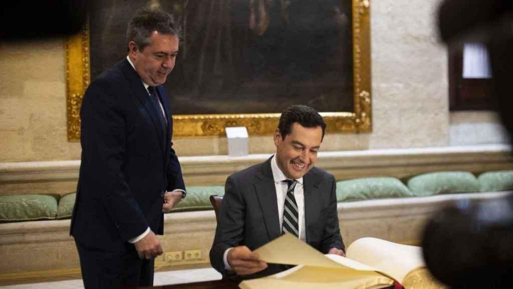 Juanma Moreno firma en el libro de visitas del Ayuntamiento de Sevilla junto a Juan Espadas.