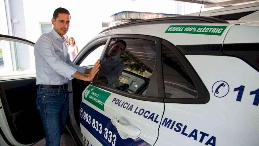 El alcalde de Mislata, Carlos Fernández, junto a un coche de la Policía Local. EE