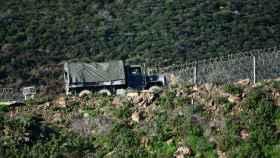Un camión del ejército marroquí patrulla frente al tramo del vallado que separa España de Marruecos, en Ceuta. EP