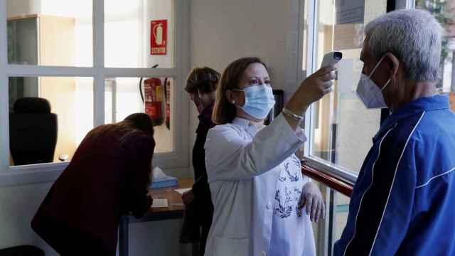 Una trabajadora toma la temperatura a un usuario a las puertas de un centro de mayores en Madrid.