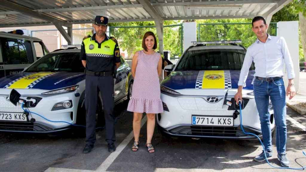 A la derecha, el alcalde de Mislata, Carlos Fernández Bielsa, enchufa un coche eléctrico de la Policía Local. EE