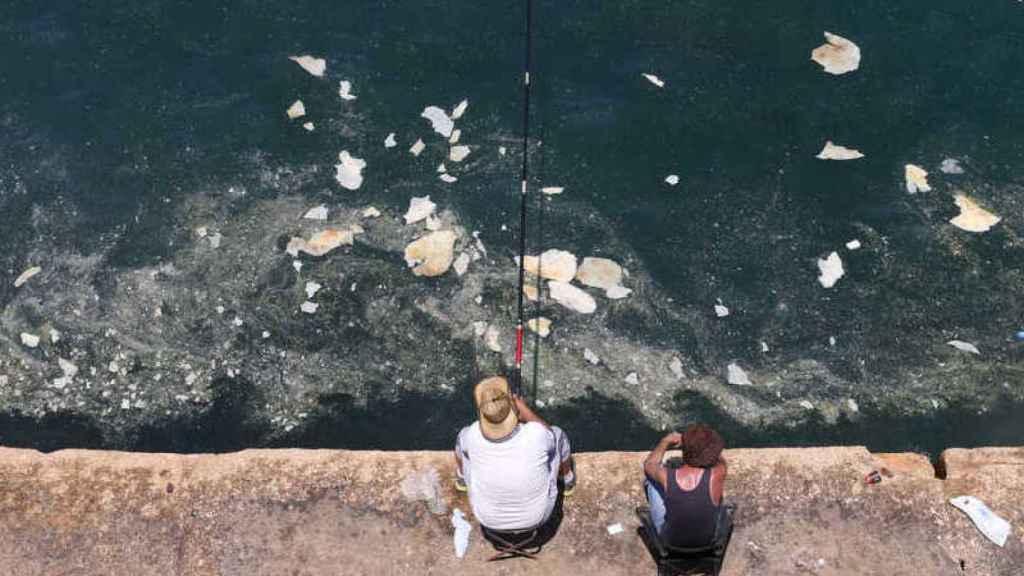 Dos personas pescan en aguas contaminadas.