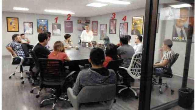 El máximo responsable de Neurona, César Hernández (de pie, en el centro), con varios carteles electorales de Podemos en su sala de reuniones.