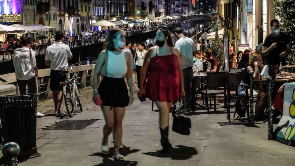 Jóvenes pasean por Milán en una concurrida zona de restaurantes.