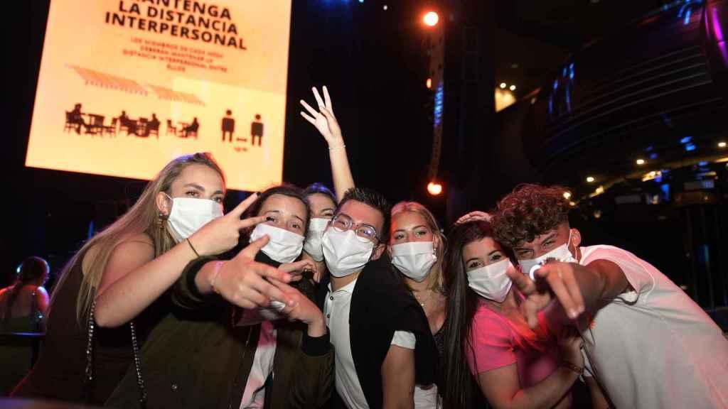 Un grupo de jóvenes usa la mascarilla dentro de una discoteca.