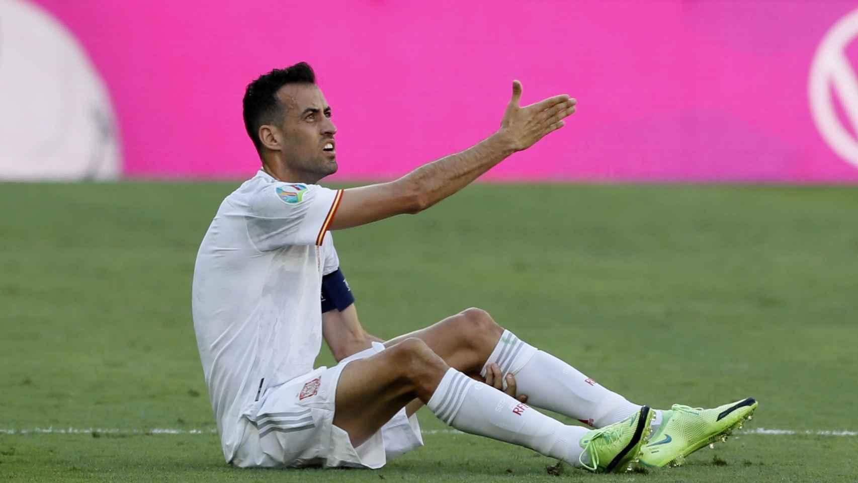 Sergio Busquets, sentado en el césped, reclama una falta al árbitro