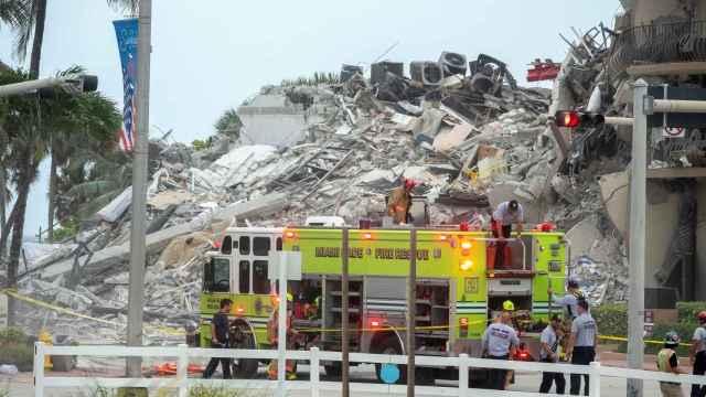 Los bomberos del condado de Miami-Dade buscan entre los escombros.