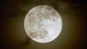 Una luna brillando en lo más alto del cielo.