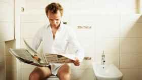 Un hombre lee el periódico sentado en el inodoro.