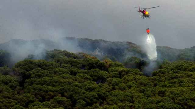 Un helicóptero sobrevolando la zona del incendio forestal en Argentona.