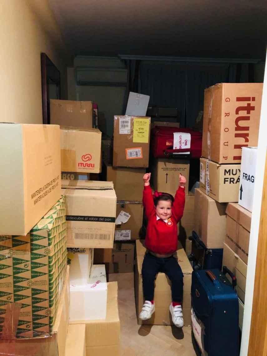 Berta, la pequeña de la casa, subida en una de las cajas con material recogido por La Estela de Ayo.