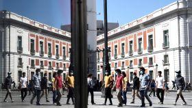 Paseantes con mascarilla reflejados en los escaparates de la Puerta del Sol.