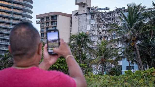 Un hombre fotografía los destrozos del edificio de 12 pisos derrumbado en Miami.