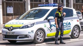 Una agente de la Policía Local de Málaga junto a un coche patrulla.