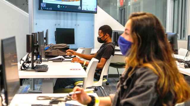 Dos jóvenes con mascarilla utilizando un ordenador durante una clase