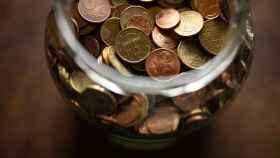 Un frasco con monedas de euro de distintas denominaciones.