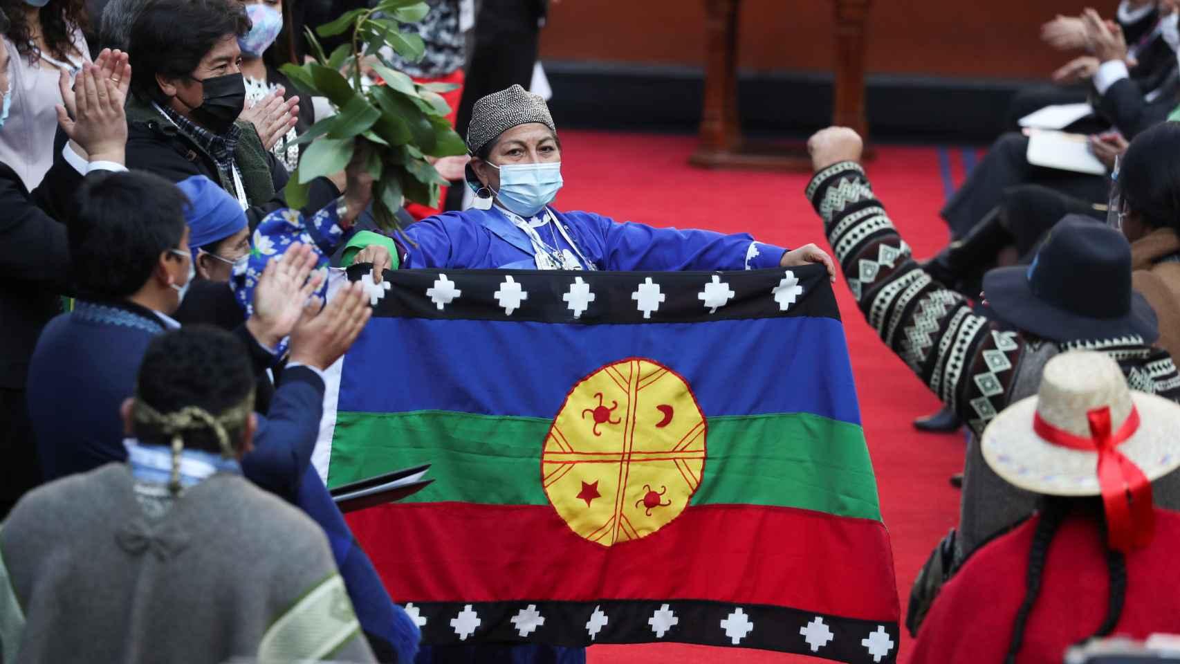 Elisa Loncón sostiene la bandera mapuche .