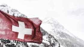La bandera de Suiza con las montañas nevadas al fondo.