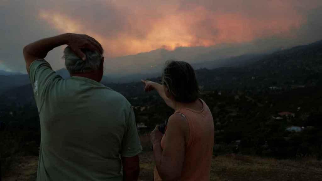 Dos personas en el distrito de Lárnaca contemplan el incendio que ha arrasado Chipre.