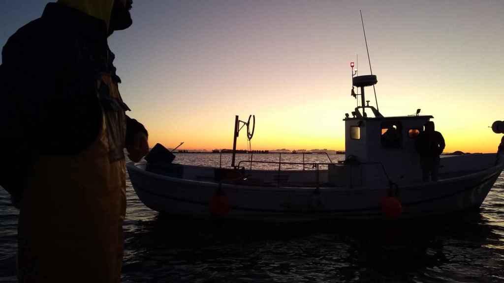 'Al amanecer': Los primeros rayos de sol que bañan el Mar Menor dibujan la silueta de Manolo, patrón de la 'Begoñita', charlando con otros pescadores que han salido a pescar lubina mediante métodos tradicionales.
