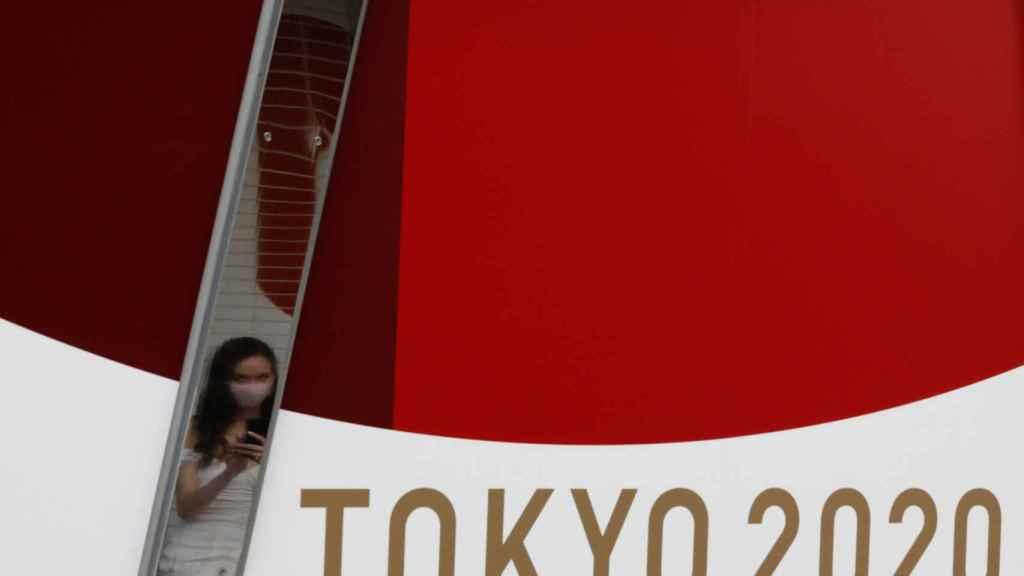 Una mujer se protege con su mascarilla cerca de un poster de los Juegos Olímpicos de Tokio 2020