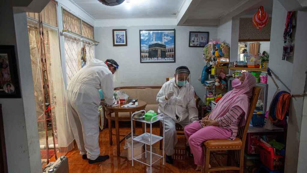 Trabajadores médicos hacen un test de coronavirus a una persona en Bogor, cerca de Yakarta.