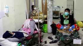 Ciudadanos de Indonesia con Covid utilizan una bombona de oxígeno.