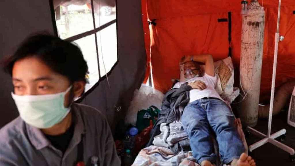 Un paciente de Covid-19 descansa en una tienda temporal fuera de la sala de emergencias de un hospital en Yakarta, Indonesia.