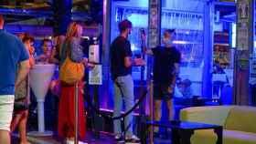Un empleado toma la temperatura a un joven al entrar a una discoteca.