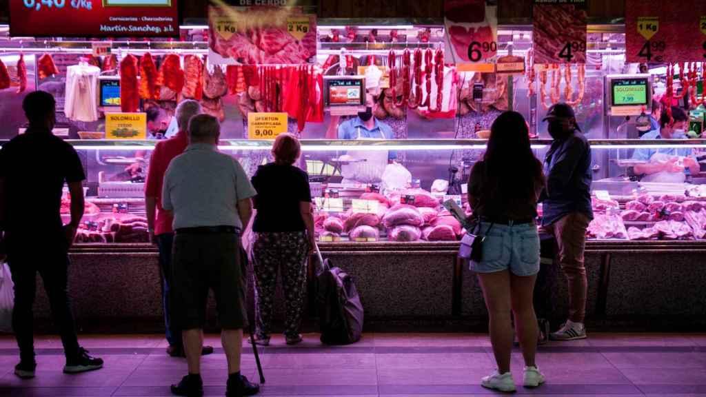 Varias personas hacen cola en una carnicería del Mercado de las Maravillas de Madrid.