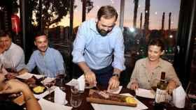 Paco Nuñez cortando una pieza de carne durante una cena con alcaldes del PP