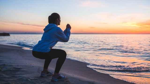 Una mujer hace sentadillas en la playa.